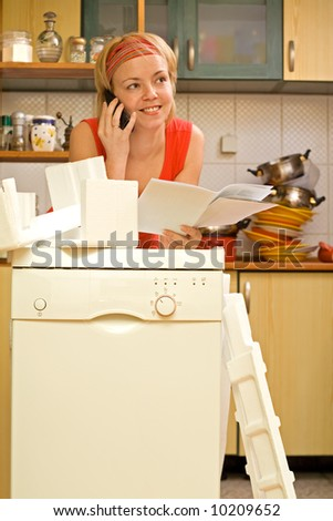 Happy woman on the phone, propping against her new kitchen appliance - a dishwasher