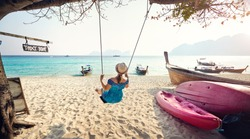 Happy woman on the swing at the tropical beach on Phi Phi Island in Southern Thailand. Travel magazine concept.