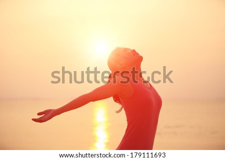 happy woman open arms under the sunrise at sea  #179111693