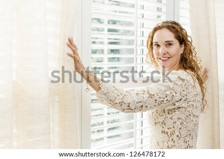 Happy woman opening curtains on big sunny window with shutters