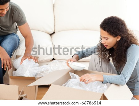 Happy woman packing glasses with her husband in the living-room for their removal