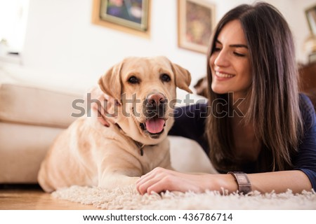 Happy woman petting her yellow labrador at home