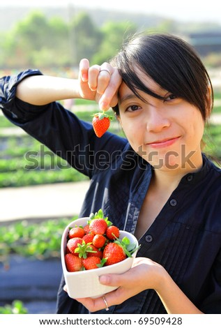 happy woman pick strawberry