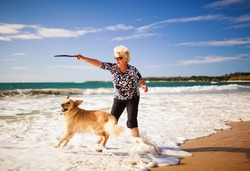 Happy woman playing on the beach with golden retriever