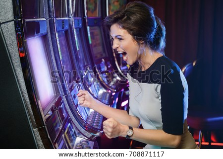 Happy woman playing slot machines in the casino - Shutterstock ID 708871117