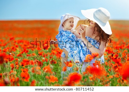 Happy woman playing with her child in a field of poppies
