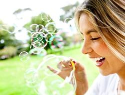 Happy woman portrait blowing soap bubbles at the park