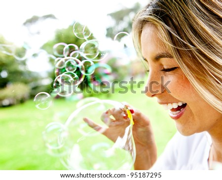Happy woman portrait blowing soap bubbles at the park