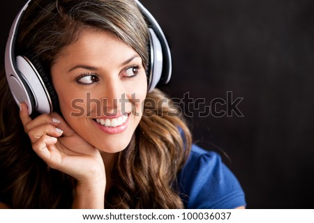 Happy woman portrait with headphones - isolated over a black background