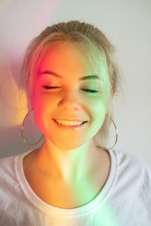 Happy woman. Positive mind. Sunny days. Enjoy moment. Smiling blonde lady catching sunshine plashes closing eyes on neutral blur rainbow glowing neon lights background.