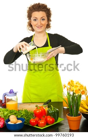 Happy woman pouring milk over flourwith eggs and baking