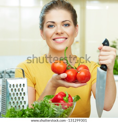 Happy Woman prepare  vegetarian food,  standing against  home kitchen interior background. Yellow color clothes. Woman Face close up portrait.