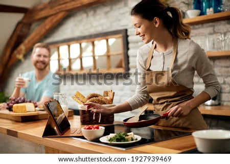Happy woman preparing food while following recipe on digital tablet in the kitchen.