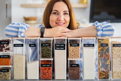 Happy woman professional space organizer smiling posing with plastic case boxes for comfortable product storage. Cute female enjoying healthy food organization, placing and sorting and kitchen