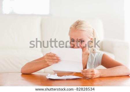 Happy woman reading a letter in her living room
