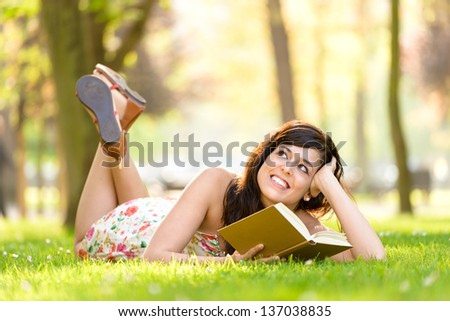 Happy woman reading and holding  story book in fresh green park on spring or summer. Caucasian brunette beautiful girl smiling and day dreaming lying down outdoors.