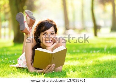 Happy woman reading and holding  story book in fresh green park on spring or summer. Caucasian brunette beautiful girl smiling and day dreaming lying down on grass outdoors.