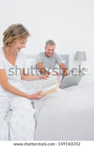 Happy woman reading book while husband is using laptop in bedroom at home