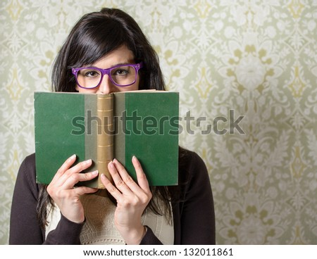 Happy woman reading.  Girl looking over old book on retro background. Student smiling behind old book wearing glasses.