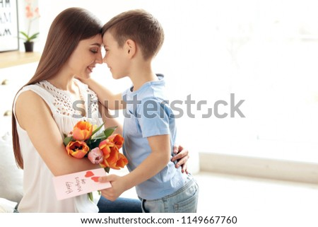Happy woman receiving flowers and greeting card from her son at home. Mother's day celebration #1149667760
