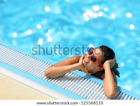 Happy woman relaxing and enjoying summer at pool. Beautiful brunette caucasian girl with red sunglasses on summer vacation into swimming pool. Copy space.