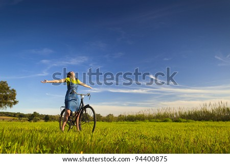 Happy woman relaxing and sitting on a bicycle, in a green meadow