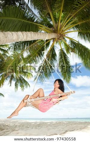 Happy woman relaxing in hammock on a tropical beach