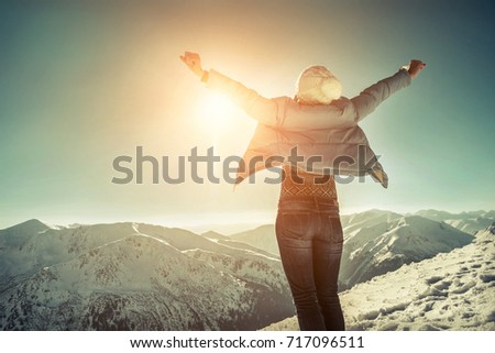 Happy woman relaxing on the top of mountain under blue sky with sunlight at sunny winter day, travel vacation, landscape mountains background. #717096511