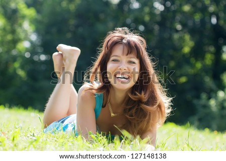 Happy   woman  relaxing outdoor in grass