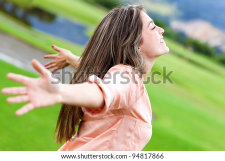 Happy woman relaxing outdoors with arms open