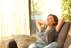 Happy woman resting comfortably sitting on a couch in the living room at home