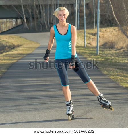 Happy woman roller skating sport smiling in park sunny day - stock photo