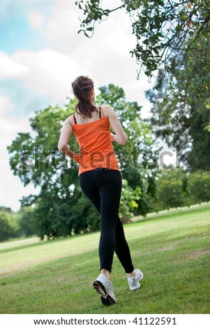 Happy woman running at the park with sportswear