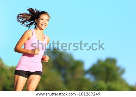 Happy woman running in city park. Asian girl runner jogging smiling aspirational outside on beautiful summer day. Mixed race Asian Chinese / Caucasian female fitness sport model training outdoors.