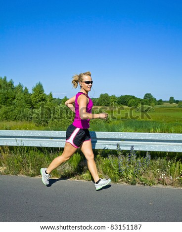 Happy woman running on country road in sunny summer