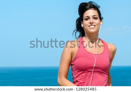 Happy woman running on summer on sea background. Female caucasian fitness athlete jogging.