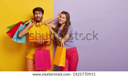 Happy woman satisfied after successful shopping, puzzled man holds many colorful bags and box, make purchase on black Friday, visit shopping mall in day of sales and discounts. Consumerism, purchasing