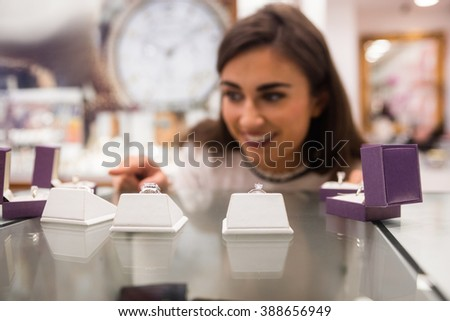 Happy woman selecting a finger ring in a jewelry shop