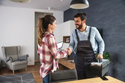 Happy woman shaking hands with repairman. Home interior.