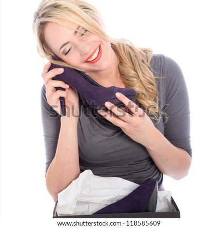 Happy woman shopper caressing a newly purchased and unwrapped shoe with her cheek with a look of bliss isolated on white