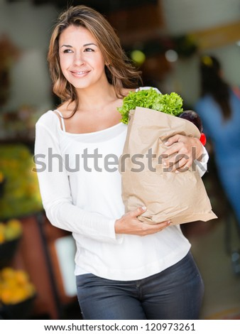 Happy woman shopping carrying a bag with groceries
