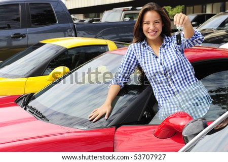 happy woman showing key of new sports car