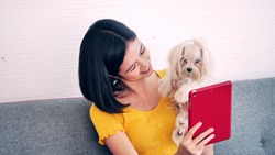 Happy woman sitting and taking a photo by tablet with shihtzu dog on a sofa at home
