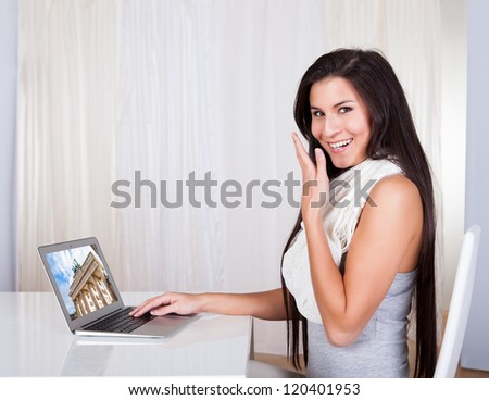 Happy woman sitting at her desk shopping online browsing travel sites