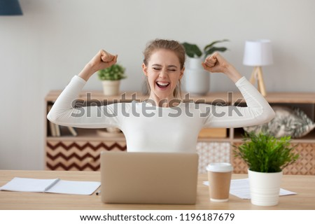 Happy woman sitting at the desk opposite laptop. Excited female feels happy received a scholarship, took on a good post or passed an examination. Positive emotions showing gesture Yes I did it concept