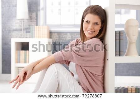 Happy woman sitting in smart living room at bookshelf, smiling at camera.?