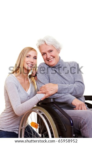Happy woman sitting in wheelchair with young nurse to her side