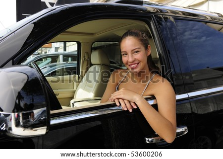 happy woman sitting inside of her new expensive 4x4 off-road vehicle