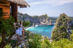 Happy woman sitting near tree house at viewpoint Thousand Island. Travel destination in Bali, Indonesia. Popular place to visit on Nusa Penida island.