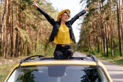 Happy Woman Sitting on Car Sunroof Freedom Concept. Road Trip Joy. Hipster Beautiful Caucasian Girl with Raised Arms on Yellow Vehicle Roof. Wanderlust Adventure at Summer Weekend. Carefree Lifestyle
